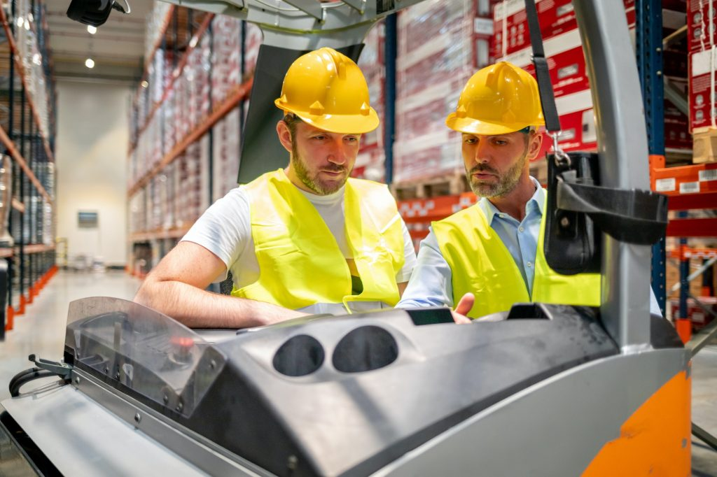 Warehouse worker learns how to use forklift with instructor