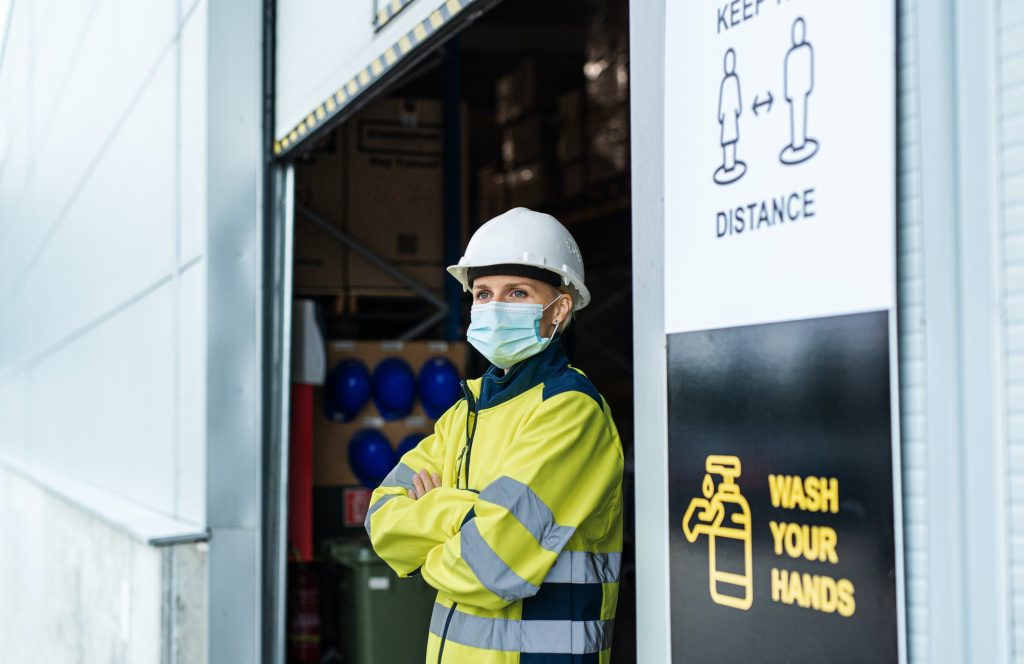 Woman worker with face mask standing in front of warehouse, coronavirus concept.